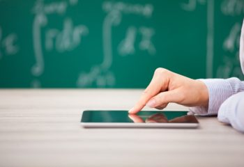 Flexible Teaching in 2017 teachers close up of teacher's hand touching a tablet on a desk in a classroom with a blackboard and writing in the background