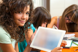 Young Teenage girl holding interactive screens for schools in a classroom environment